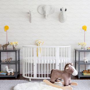 Diseño de habitación de bebé neutra tradicional renovada con paredes multicolor, suelo de madera oscura y suelo marrón