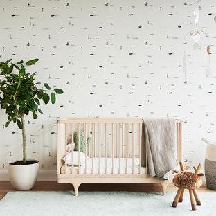 Modelo de habitación de bebé neutra escandinava con paredes multicolor y suelo de madera clara