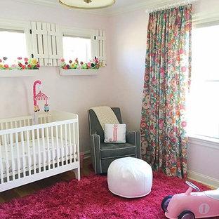 Inspiration pour une chambre de bébé fille traditionnelle de taille moyenne avec un mur rose et un sol en bois brun.