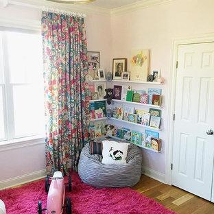 Imagen de habitación de bebé niña tradicional renovada, de tamaño medio, con paredes rosas y suelo de madera en tonos medios