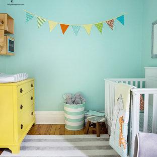 Ejemplo de habitación de bebé neutra pequeña con paredes verdes, suelo de madera clara y suelo amarillo