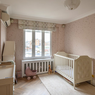 Inspiration for a medium sized classic nursery for girls in London with pink walls, medium hardwood flooring and brown floors.