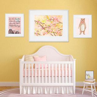 Imagen de habitación de bebé niña minimalista con paredes amarillas, suelo de madera en tonos medios y suelo marrón