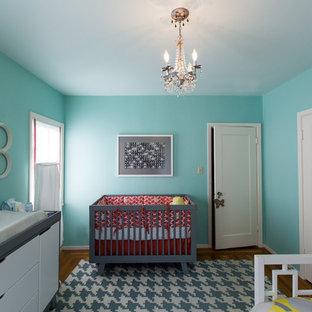 Réalisation d'une chambre de bébé neutre design de taille moyenne avec un mur bleu et un sol en bois brun.