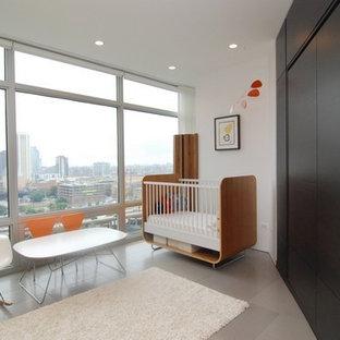 Imagen de habitación de bebé neutra minimalista, pequeña, con paredes blancas, suelo de baldosas de porcelana y suelo gris