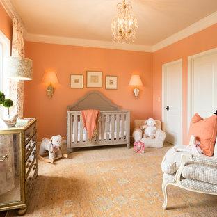 Immagine di una cameretta per neonata tradizionale di medie dimensioni con pareti arancioni, moquette e pavimento arancione