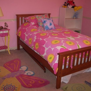 Design ideas for a medium sized eclectic nursery for girls in Chicago with pink walls and carpet.