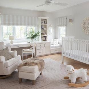 Idée de décoration pour une chambre de bébé neutre tradition de taille moyenne avec un mur blanc, un sol en bois clair et un sol beige.