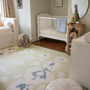 Mid-sized country girl medium tone wood floor nursery photo in New York with gray walls