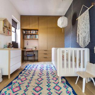 Ispirazione per una cameretta per neonati neutra moderna di medie dimensioni con pareti grigie, pavimento in laminato, pavimento beige e pareti in mattoni