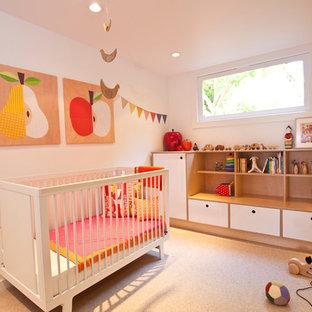 Immagine di una cameretta per neonata scandinava con pareti bianche e moquette