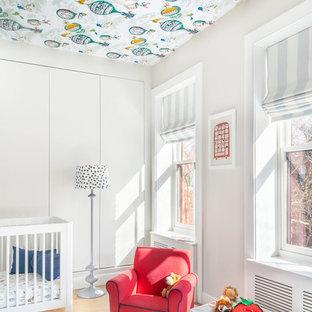 Ejemplo de habitación de bebé tradicional renovada con paredes grises, suelo de madera en tonos medios y suelo marrón