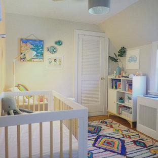 Cette image montre une petit chambre de bébé neutre bohème avec un mur orange et un sol en bois brun.