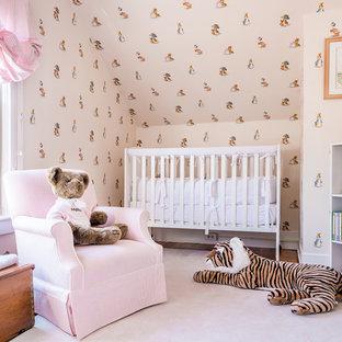 Diseño de habitación de bebé campestre con paredes beige, suelo de madera en tonos medios y suelo rosa