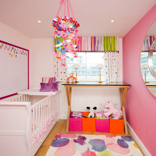 Small traditional nursery for girls in London with pink walls and medium hardwood flooring.