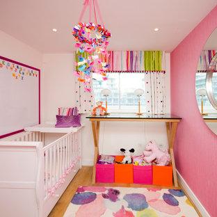 Exempel på ett litet klassiskt babyrum, med rosa väggar och mellanmörkt trägolv