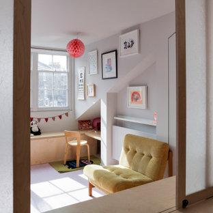 Immagine di una piccola cameretta per neonati neutra contemporanea con pareti grigie, pavimento in legno verniciato, pavimento rosa e pannellatura