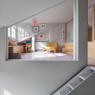 Esempio di una piccola cameretta per neonati neutra minimal con pareti grigie, pavimento in legno verniciato, pavimento rosa e pannellatura
