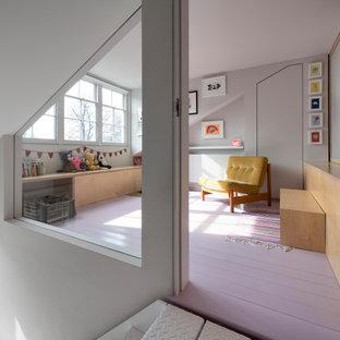 Стильный дизайн: маленькая нейтральная комната для малыша в современном стиле с серыми стенами, деревянным полом, розовым полом и панелями на части стены - последний тренд