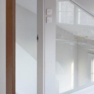 Inspiration pour une petit chambre de bébé neutre design avec un mur gris, un sol en bois peint, un sol rose et du lambris.