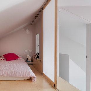 Esempio di una piccola cameretta per neonati neutra contemporanea con pareti grigie, pavimento in legno verniciato, pavimento rosa e pannellatura