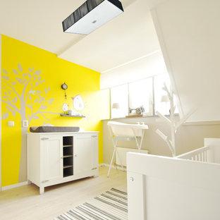 Aménagement d'une chambre de bébé neutre contemporaine avec un mur jaune, un sol en bois clair et un sol beige.