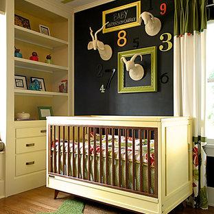 Cette photo montre une chambre de bébé neutre tendance avec un mur noir et un sol en bois foncé.