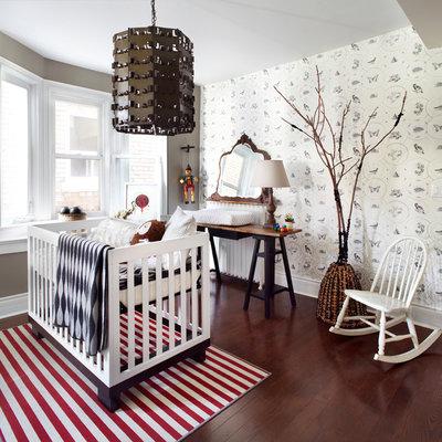 Mid-sized trendy gender-neutral dark wood floor nursery photo in Toronto with gray walls