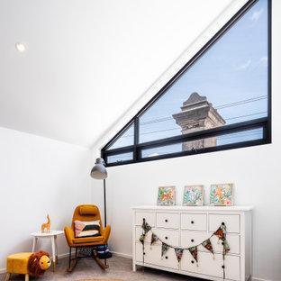 Exemple d'une petit chambre de bébé neutre tendance avec un mur blanc, moquette, un sol beige et un plafond voûté.