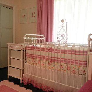Modelo de habitación de bebé niña tradicional renovada, pequeña, con paredes rosas y suelo de madera oscura