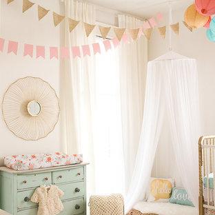 Ejemplo de habitación de bebé niña romántica, de tamaño medio, con paredes blancas y suelo de madera pintada