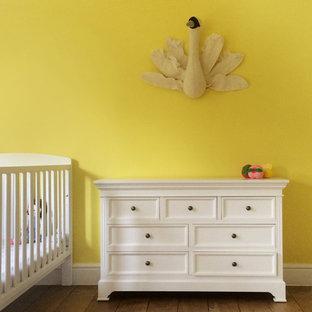 Foto de habitación de bebé neutra contemporánea, grande, con paredes amarillas, suelo de madera en tonos medios y suelo marrón