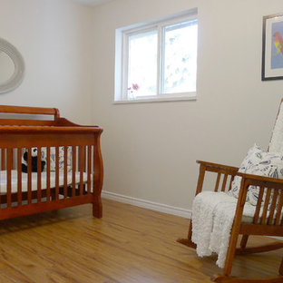 Imagen de habitación de bebé tradicional renovada, pequeña, con paredes blancas y suelo laminado