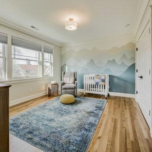Foto di una cameretta per neonati neutra american style di medie dimensioni con pareti bianche e parquet chiaro