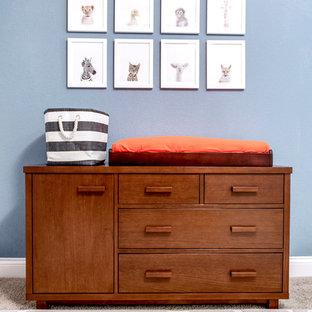 Modelo de habitación de bebé neutra bohemia, de tamaño medio, con paredes azules y moqueta