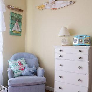 Esempio di una cameretta per neonati neutra costiera con pareti beige, pavimento in legno massello medio e pavimento arancione