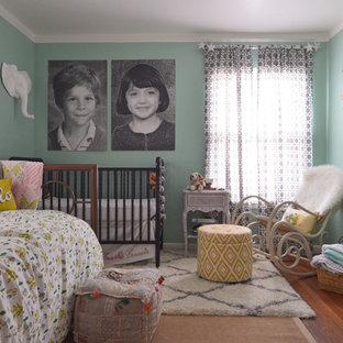 Idée de décoration pour une chambre de bébé neutre bohème de taille moyenne avec un mur vert et un sol en bois brun.