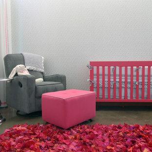 Ejemplo de habitación de bebé niña actual con paredes grises y suelo de cemento