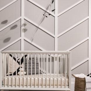 Modelo de habitación de bebé neutra vintage, de tamaño medio, con paredes grises, suelo de madera en tonos medios y suelo marrón