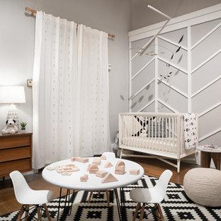 Idée de décoration pour une chambre de bébé neutre vintage de taille moyenne avec un mur gris, un sol en bois brun et un sol marron.