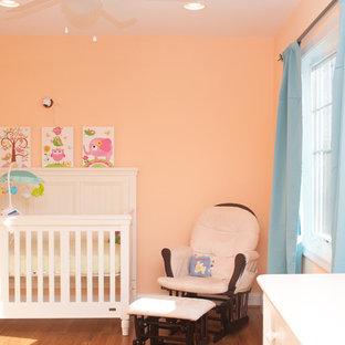 Diseño de habitación de bebé niña clásica, de tamaño medio, con parades naranjas y suelo de madera en tonos medios