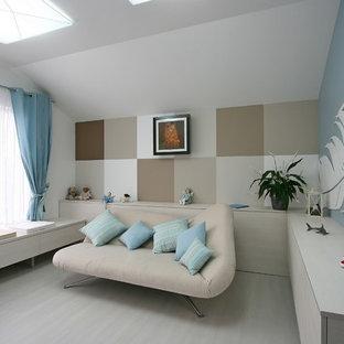 Imagen de habitación de bebé neutra actual, grande, con paredes beige y suelo de madera pintada