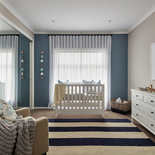 This is an example of a beach style gender-neutral nursery in Other with beige walls, carpet and beige floor.
