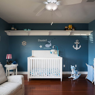 Design ideas for a medium sized beach style nursery for boys in Miami with blue walls, dark hardwood flooring and orange floors.