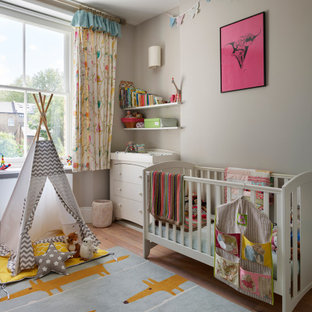 Design ideas for a contemporary gender neutral nursery in London with grey walls and light hardwood flooring.