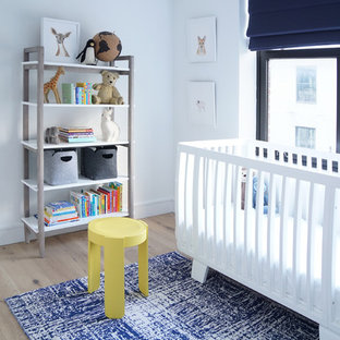 Photo of a medium sized modern nursery for boys in New York with white walls, medium hardwood flooring and brown floors.