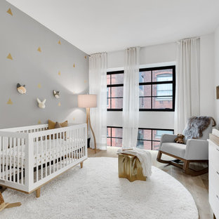 Inspiration for a contemporary light wood floor nursery remodel in New York with multicolored walls
