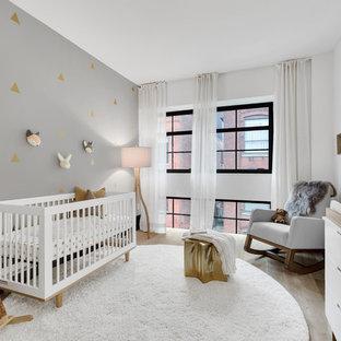 Modelo de habitación de bebé contemporánea con paredes multicolor y suelo de madera clara