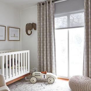 Ejemplo de habitación de bebé neutra tradicional renovada, pequeña, con paredes blancas, suelo de madera clara y suelo beige