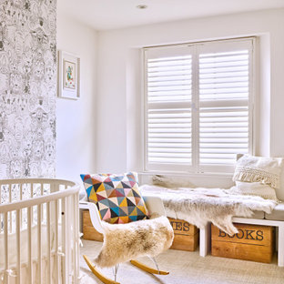 This is an example of a classic nursery in London with white walls, carpet and grey floors.